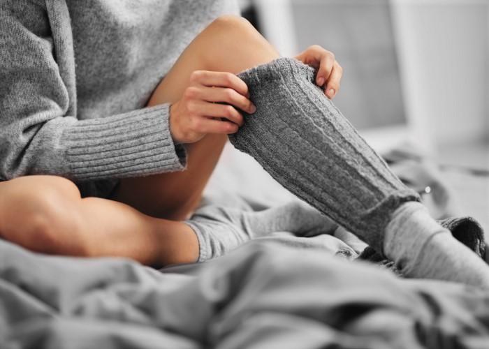 レッグウォーマーで脚を温める女性