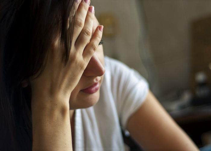 不調で頭を抱える女性