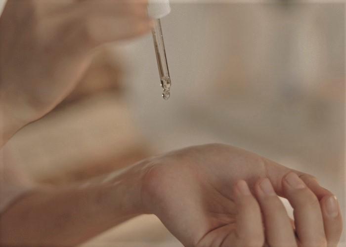 美容液をパッチテストする女性の手元